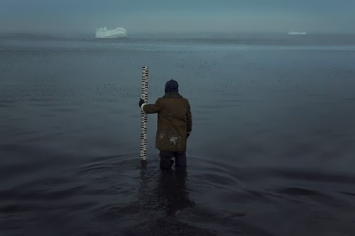 Korotkiy, standing knee-deep in water, measures the level of the Barents Sea.