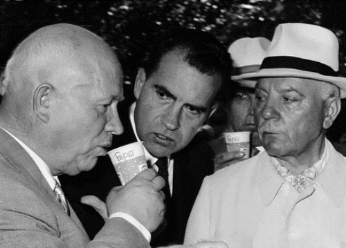 Nikita Khrushchev is tasting Pepsi-Cola, and Richard Nixon is watching his reaction. American Exhibition in Moscow in July 1959